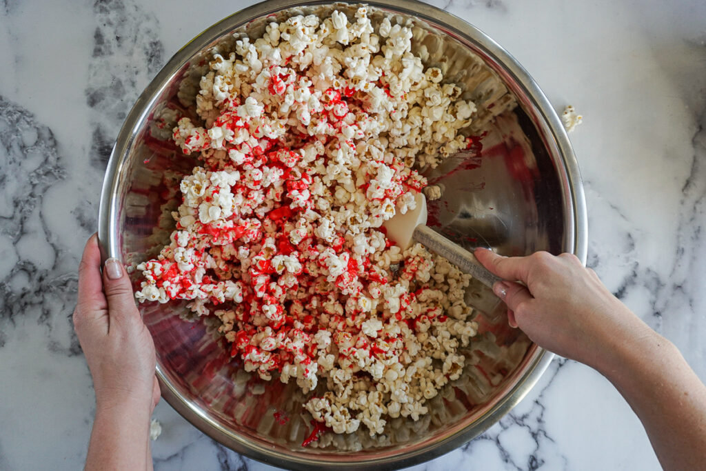 Tossing the popcorn and strawberry syrup with a spatula.