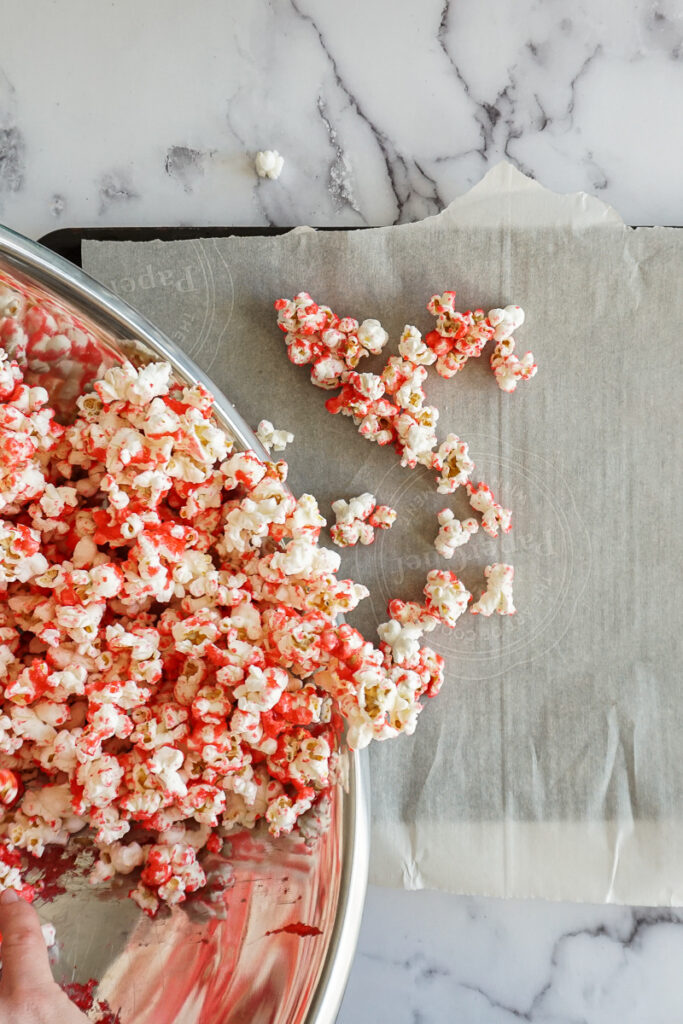 Pouring strawberry flavored popcorn onto a baking sheet.