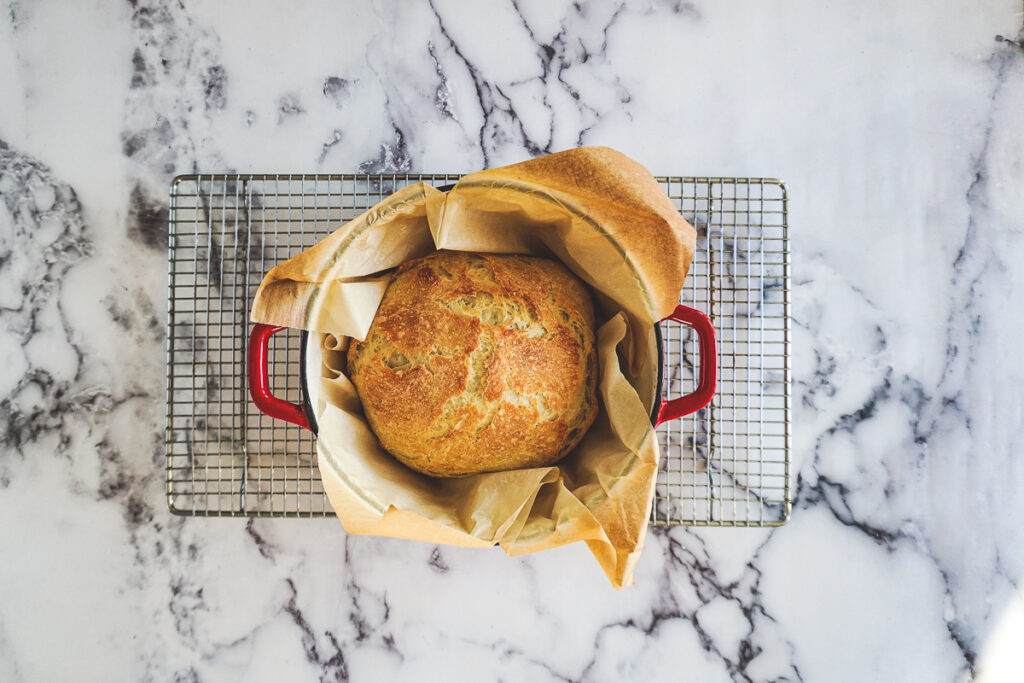Perfectly golden brown bread boule in a red dutch oven.