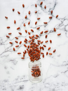 Air fryer roasted almonds spilling out of a jar.