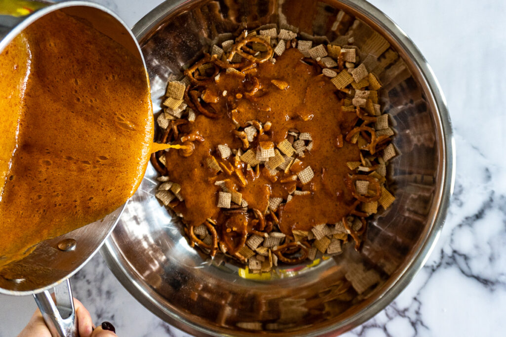 Pouring sriracha caramel on the chex, life, pretzels, and nuts in a large stainless steel bowl.
