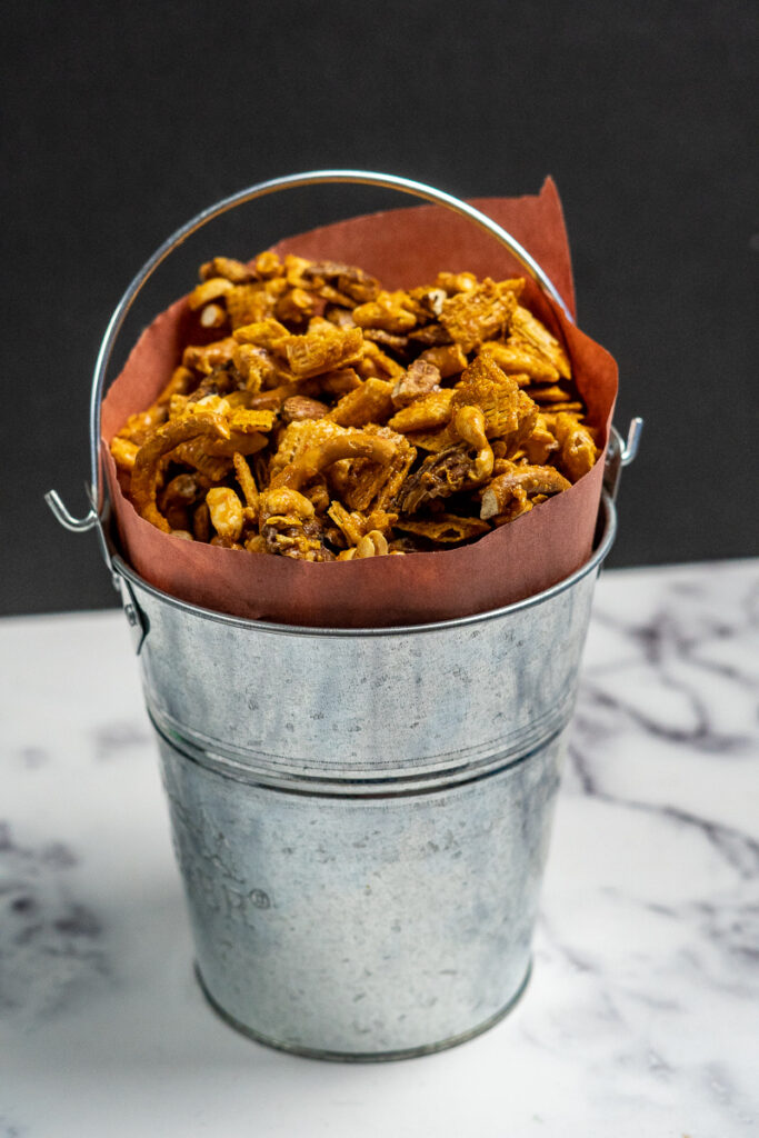 Smoked sweet and spicy chex mix in a galvanized tin bucket.