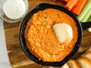 buffalo chicken dip on a tray with baguette rounds, celery and carrot sticks.