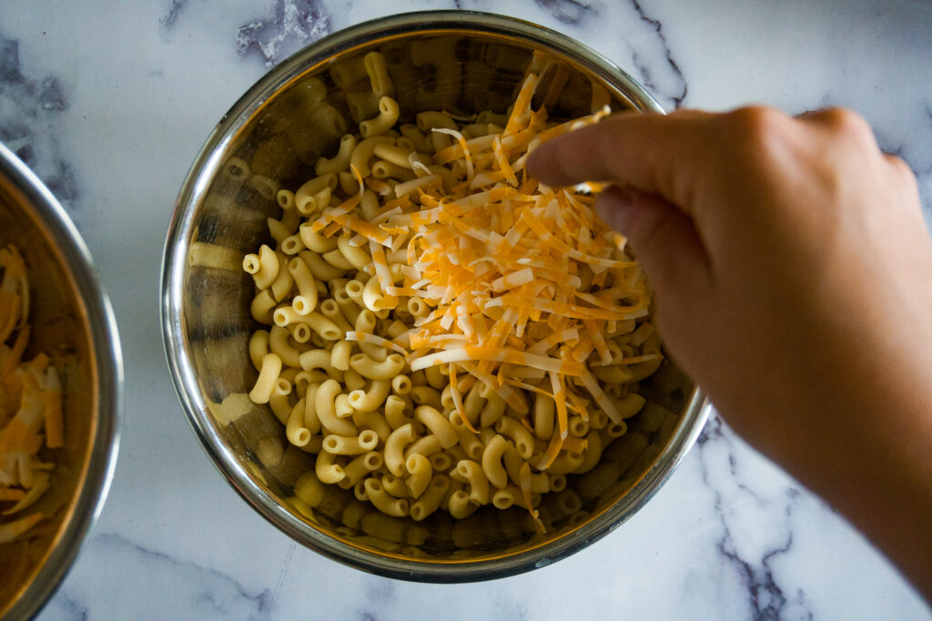 Sprinkling cheese on top of the macaroni noodles.