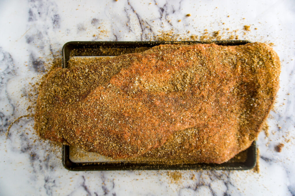 A fully rubbed brisket ready to go on the smoker.