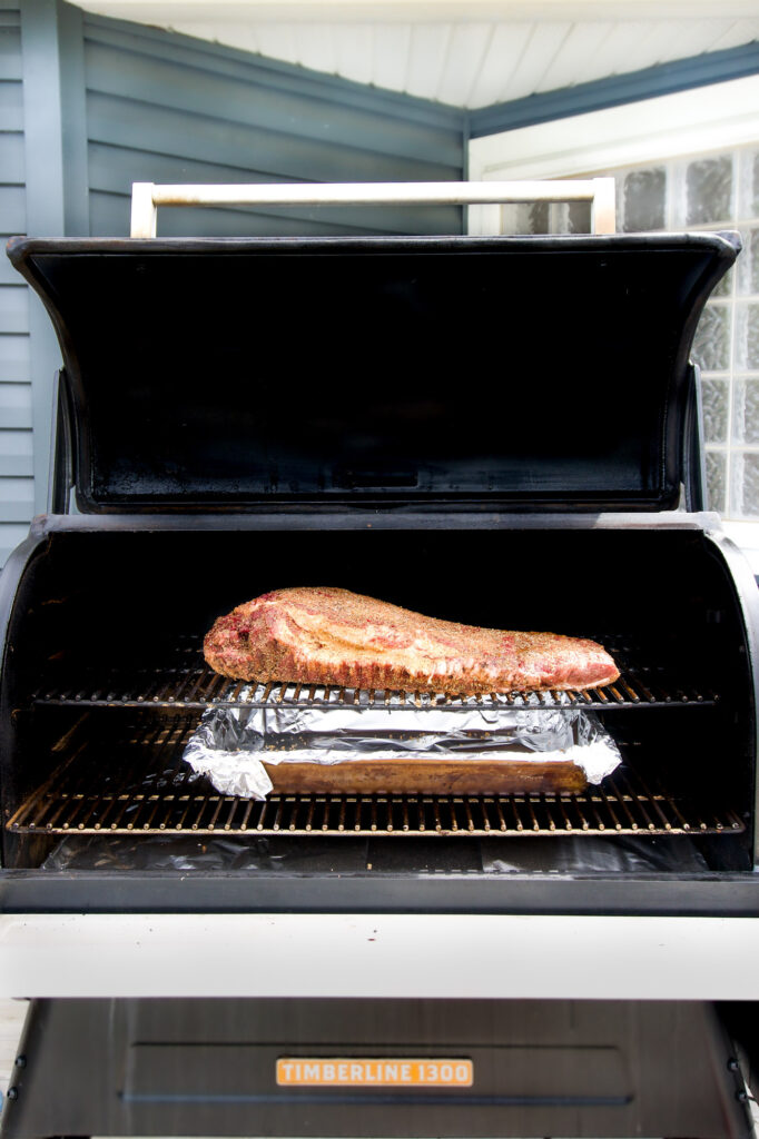 Wide open smoker filled with a massive brisket.