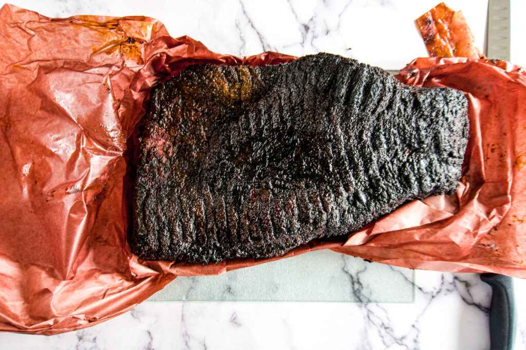Fully opened up butchers paper shwoing off a dark smoked brisket