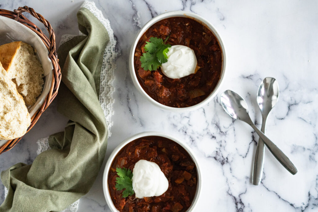 Two bowls of smoked brisket chilli with a dollop of sour cream and garnished with cilantro.