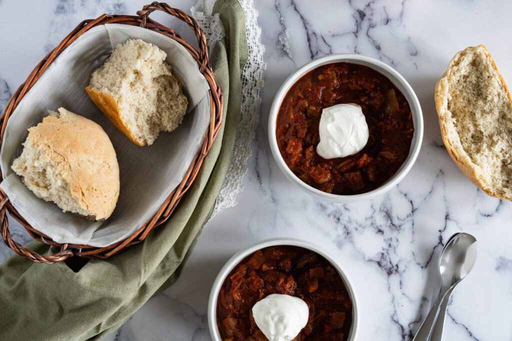 Two bowls of brisket chili with a bread basket.