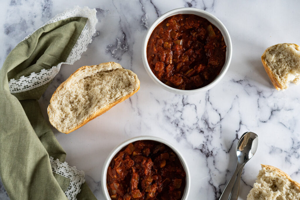 Two bowls of leftover brisket chili with bread.