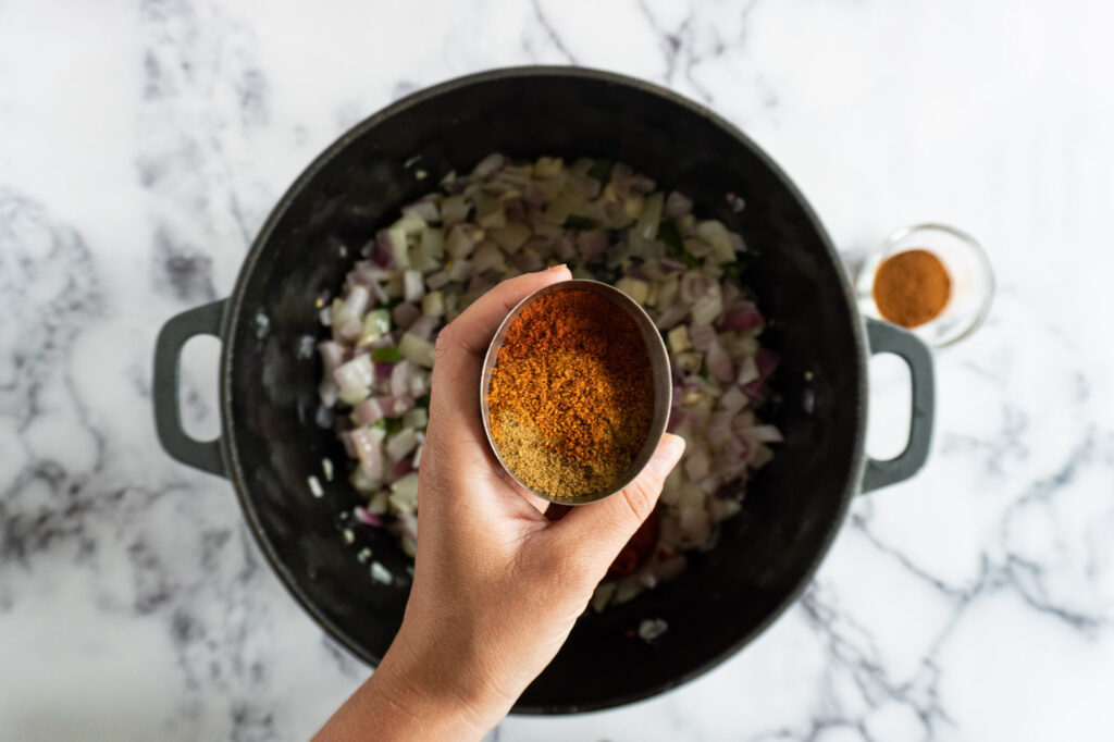 A hand holding a cup of spices over a pot filled with onions, garlic, and jalapenos.