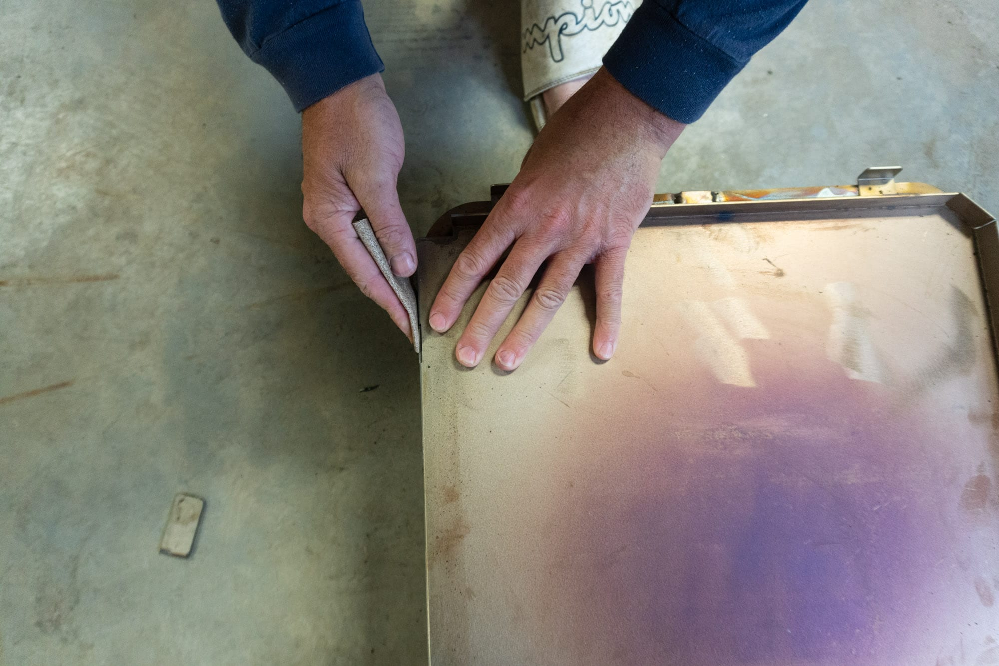 Mans's hands sanding steel burrs with sand paper.