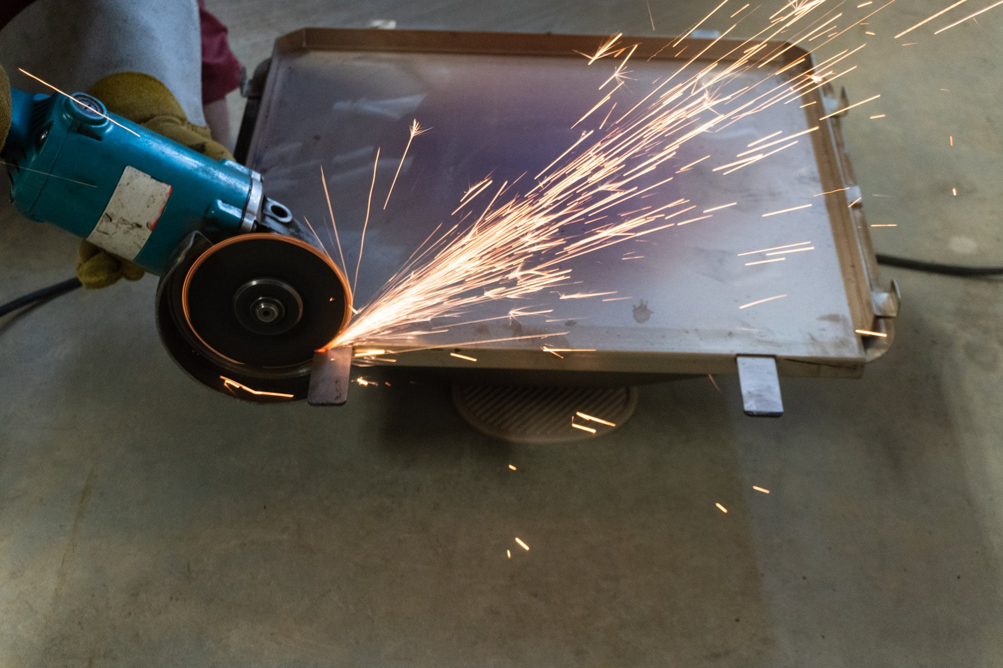 Angle grinder cutting off the front tabs of the Green Mountain pizza oven.