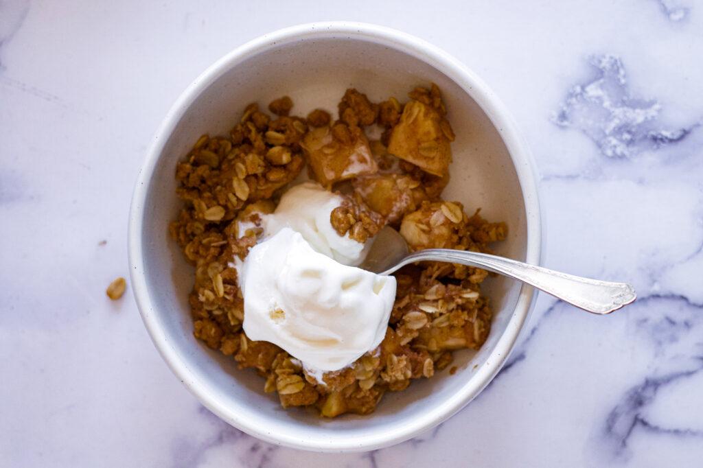 A bowl of apple crisp with ice cream