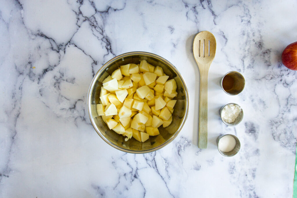 Chopped apples in a bowl with cinnamon, cornstarch and granulated sugar in small pots.