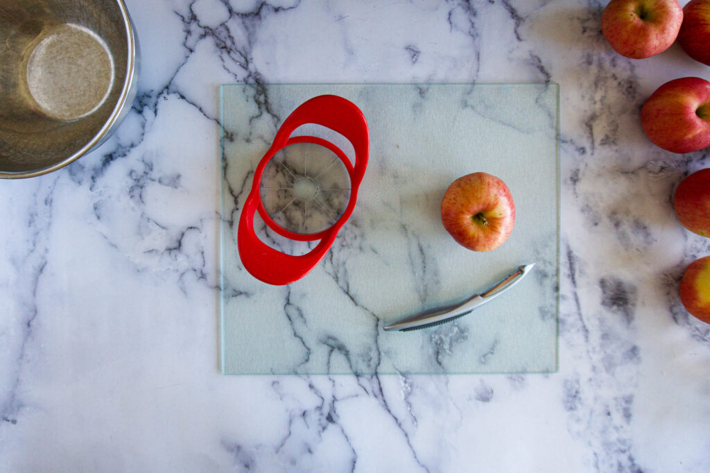 An apple corer, a peeler and and apple.