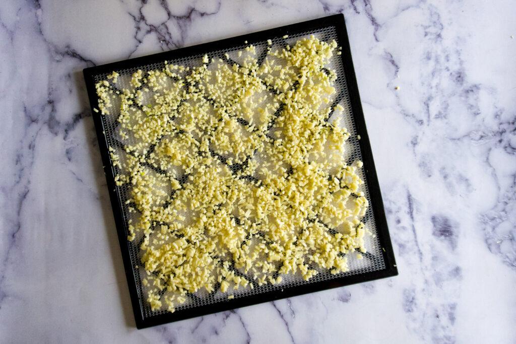 Minced garlic spread on dehydrator tray.