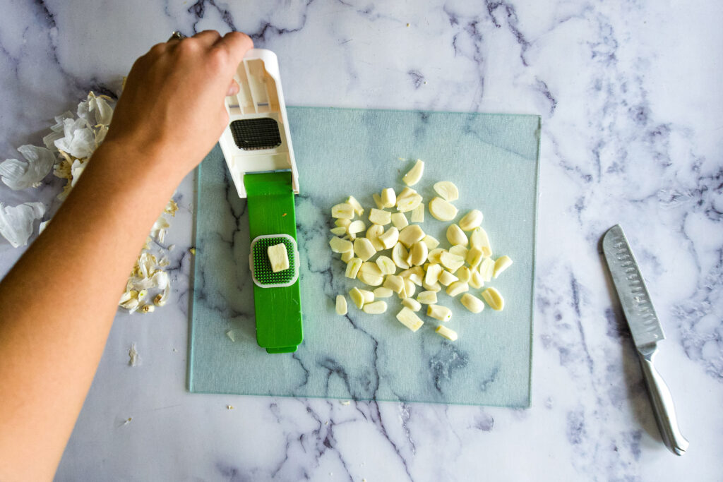 Adding garlic to the chopper.