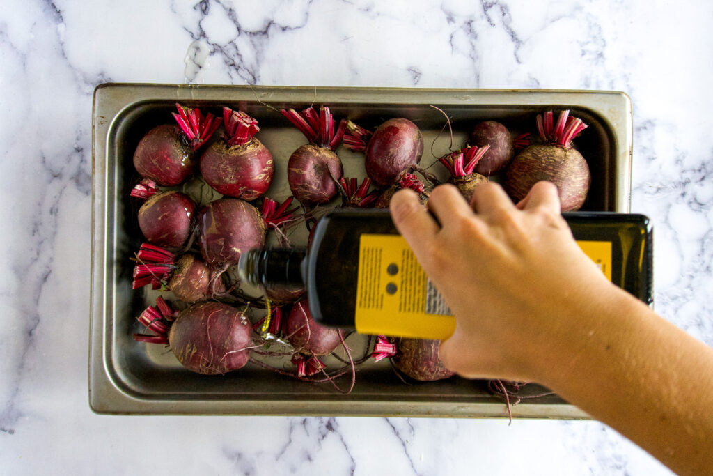 Drizzling olive oil on the beets