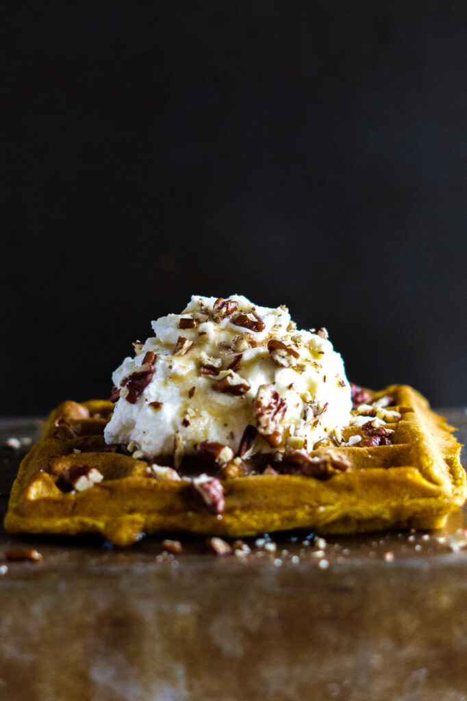 Pumpkin waffles topped with whipping cream crushed pecans and maple syrup.