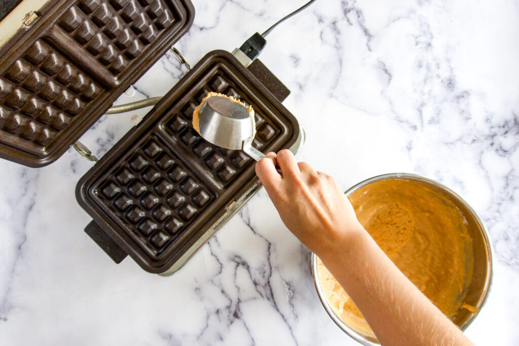 Pouring waffle batter into the iron.