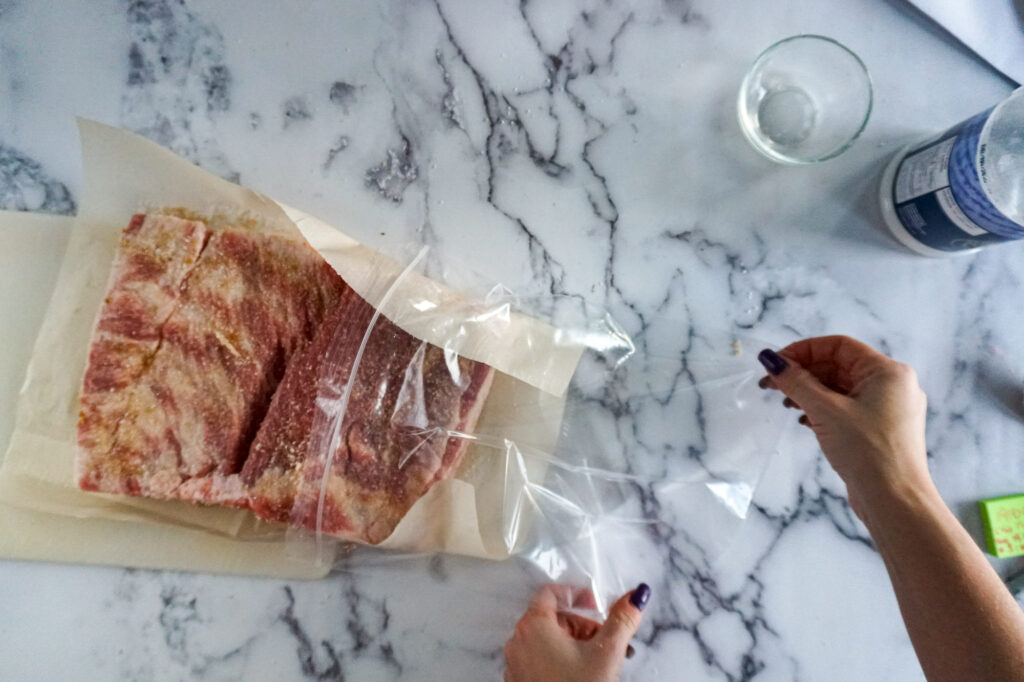 Sliding the pork belly into a ziplock bag.