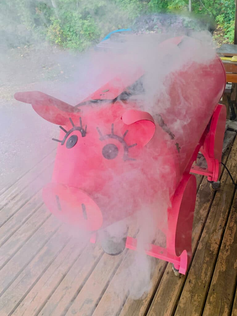 A pink pig Traeger smoking at start up.