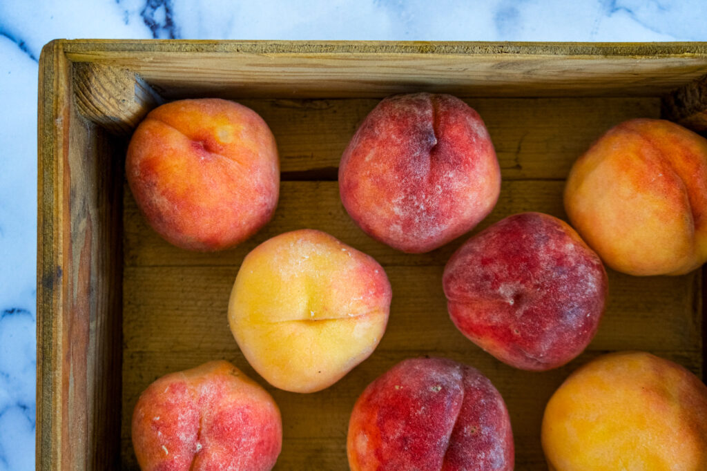 Ripe peaches in a wooden box.