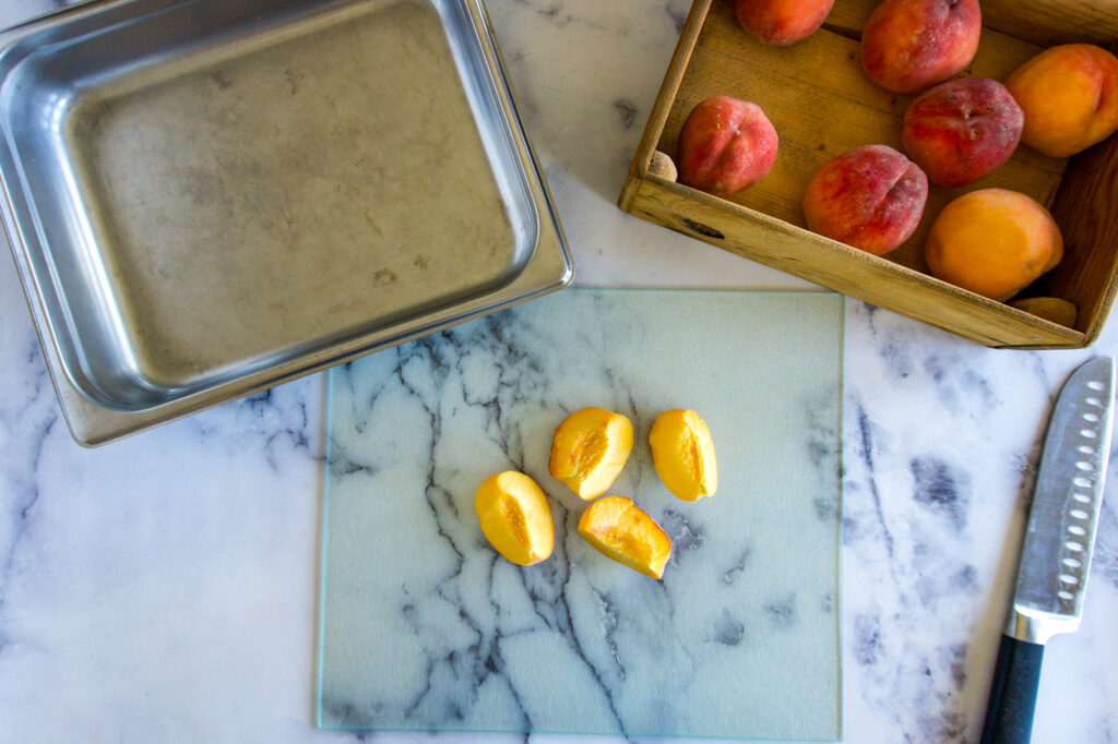 Quartered and pitted peach on a cutting board.