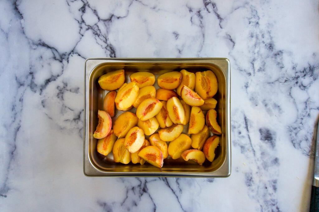 Quartered peaches in a chafing pan.