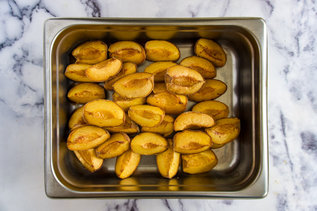 Smoked peaches in a chafing pan.
