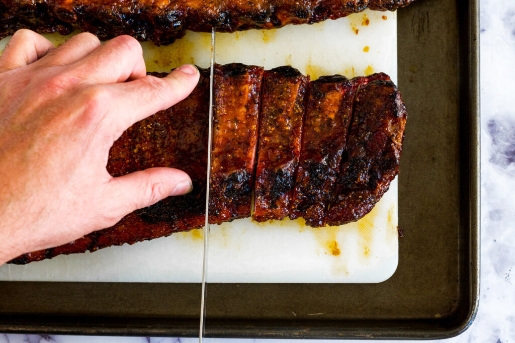 A man's hand cutting apart the ribs with a granton blade.