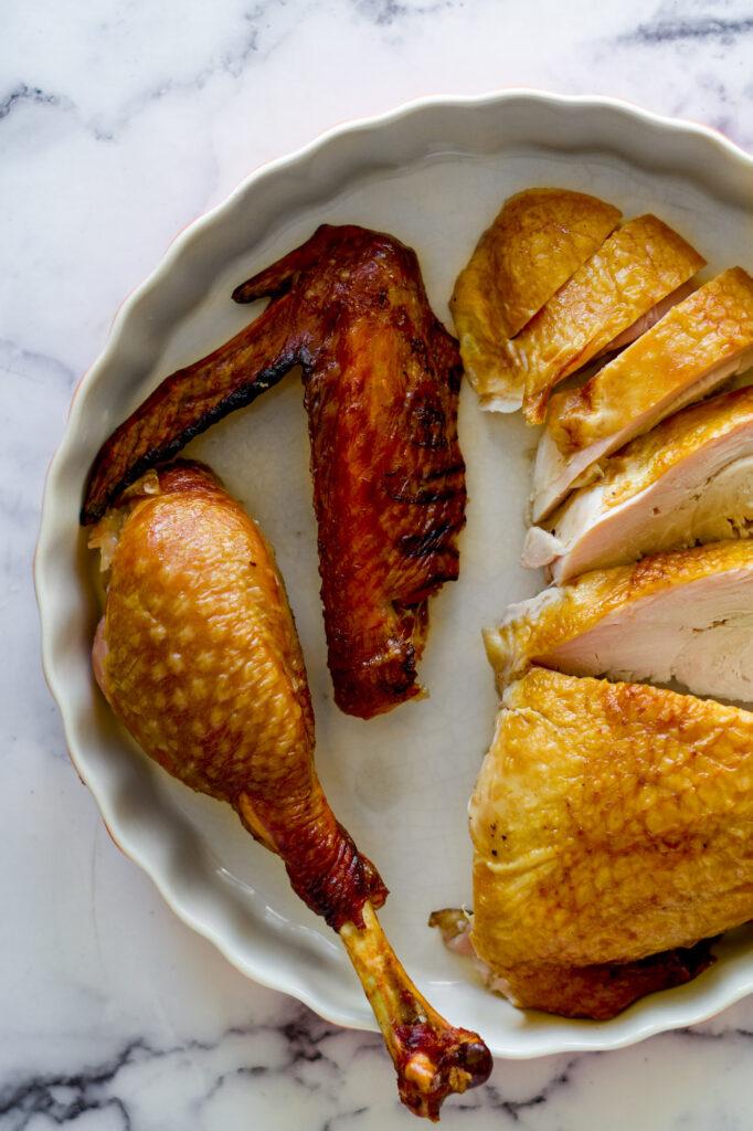 3 cuts of smoked turkey in a dish.