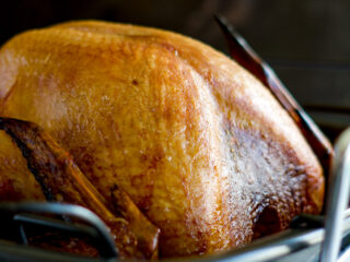 Smoked turkey in a roasting pan.