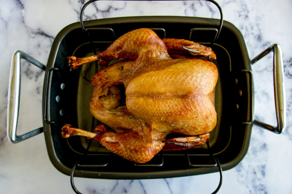 Smoked traeger turkey in a roaster.