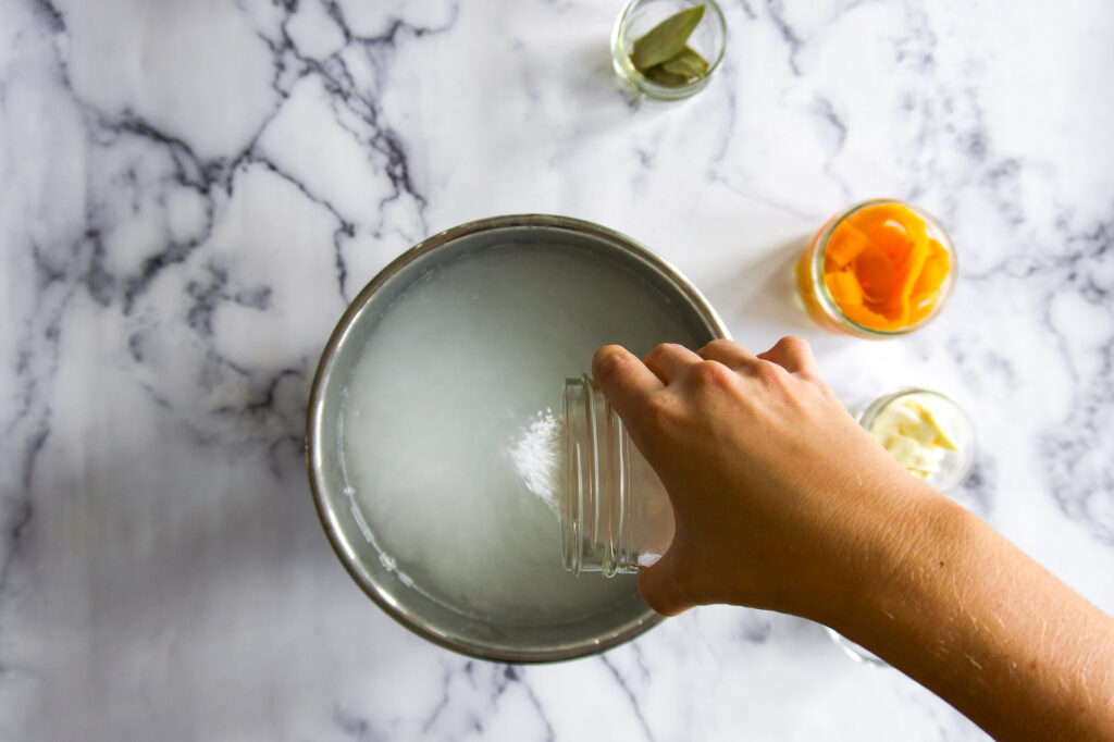 Pouring salt into the warm water.