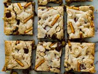 Bar snack blondies cut up on a cutting board.