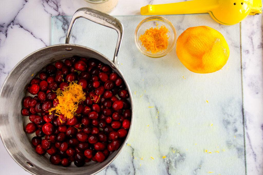 Half the orange zest on top the cranberries,