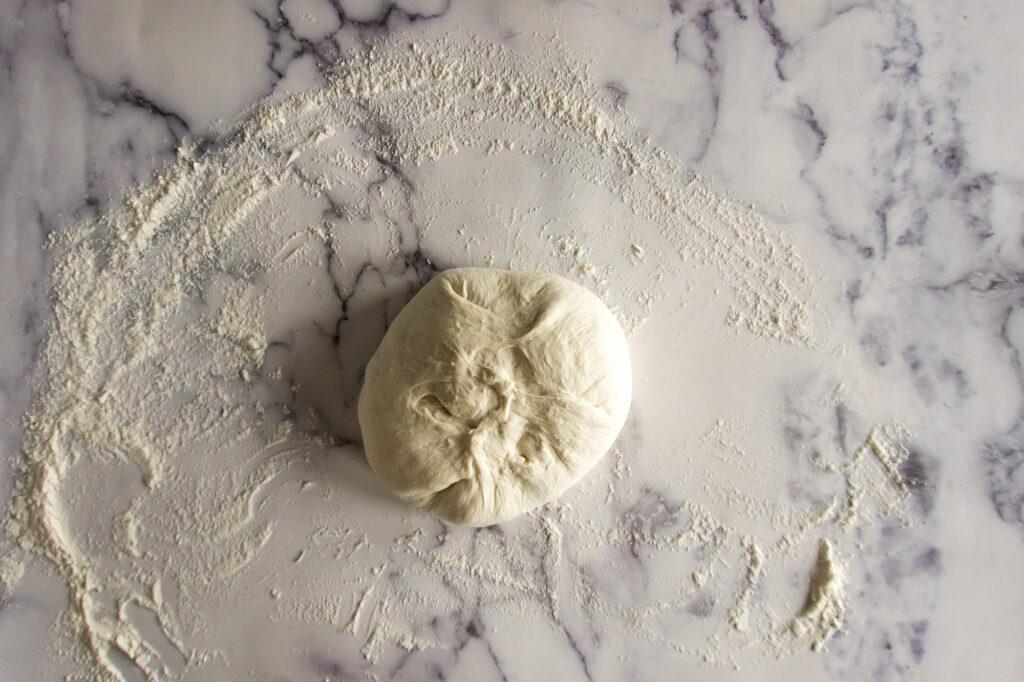 A boule on a floured surface, seam side up.