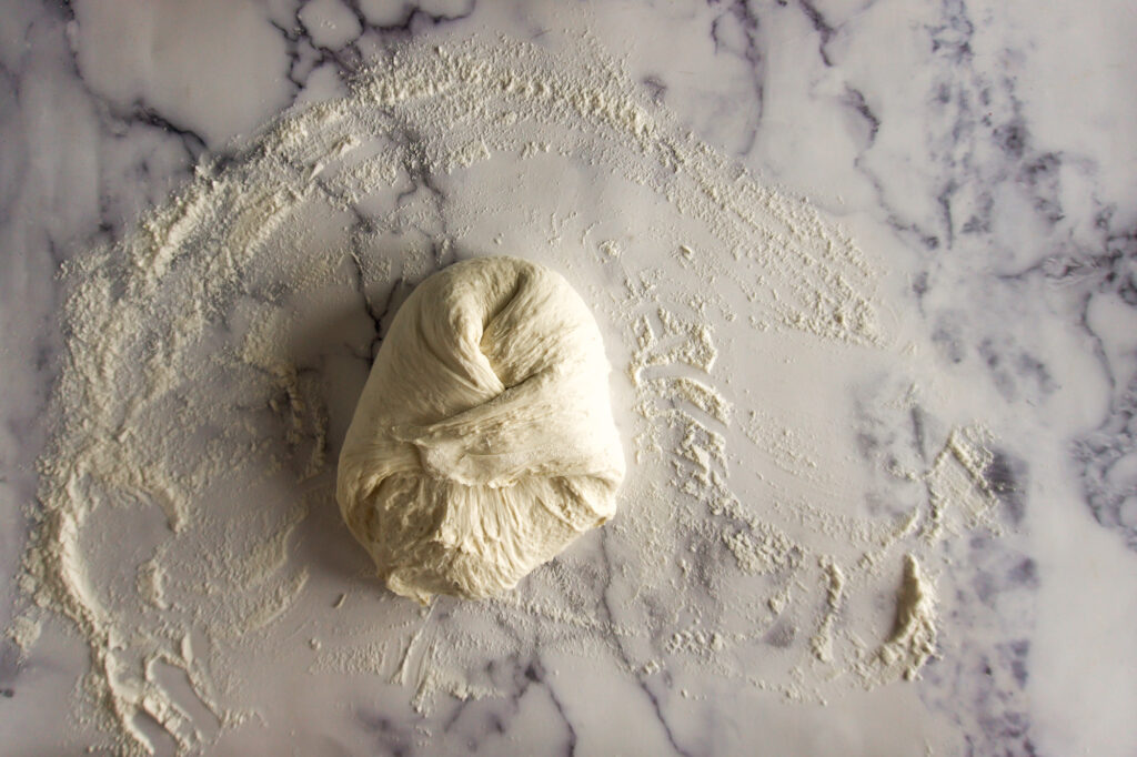 Folding the corners in on the dough.