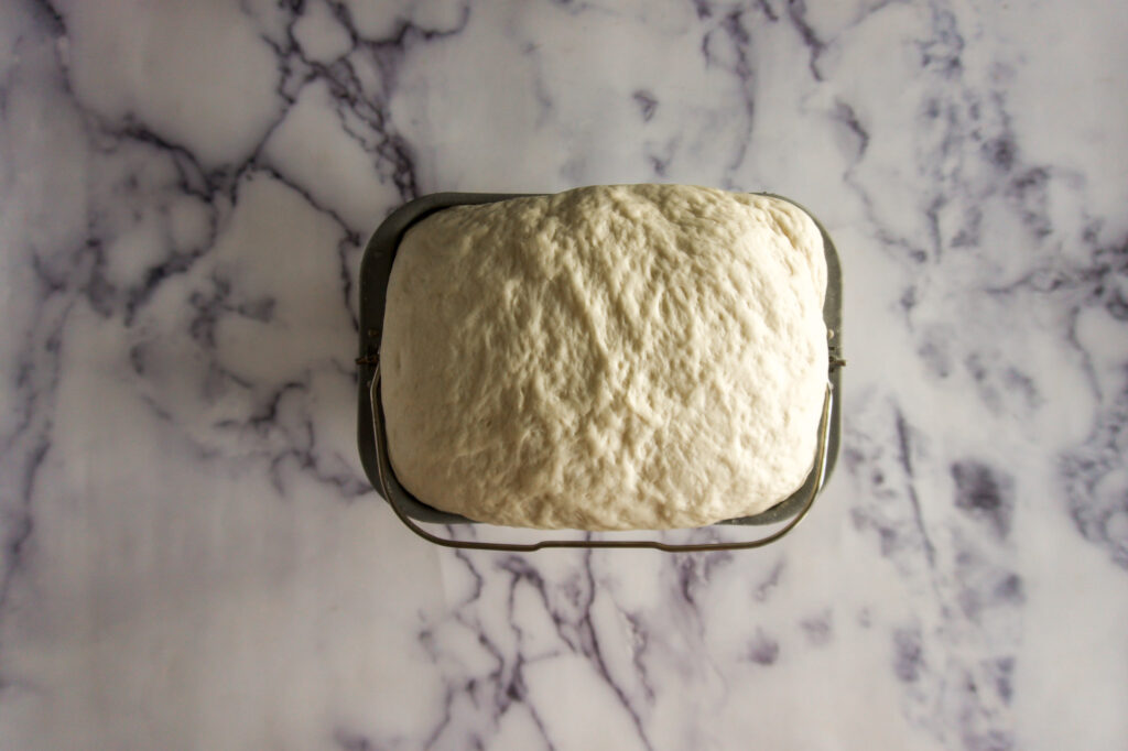 Bread dough in bread machine baking pan.