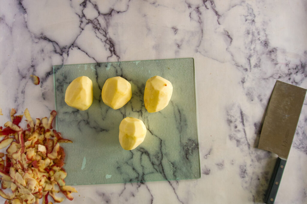 4 peeled potatoes on a cutting board.