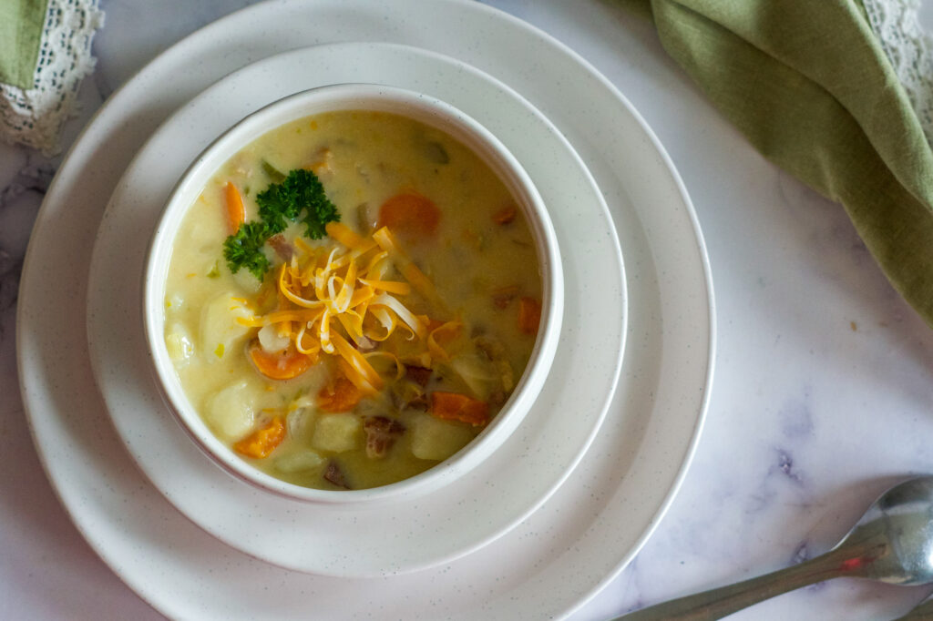 A bowl of creamy potato bacon soup with parsley and shredded cheese on top.