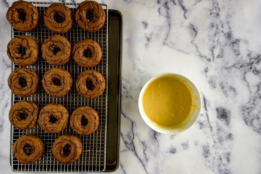 Donuts on a wire mesh cooling rack beside a bowl of glaze.