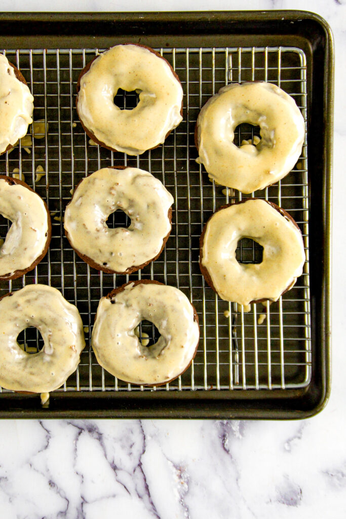 Glazed donuts on a wire mesh baking rack.
