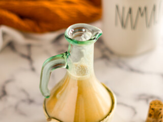 pumpkin spice coffee creamer in a small jar beside a cup of coffee.