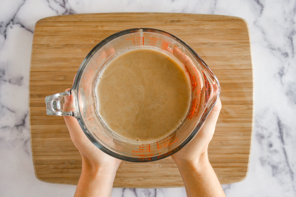 hands holding a large measuring cup full of pumpkin spice coffee cream.