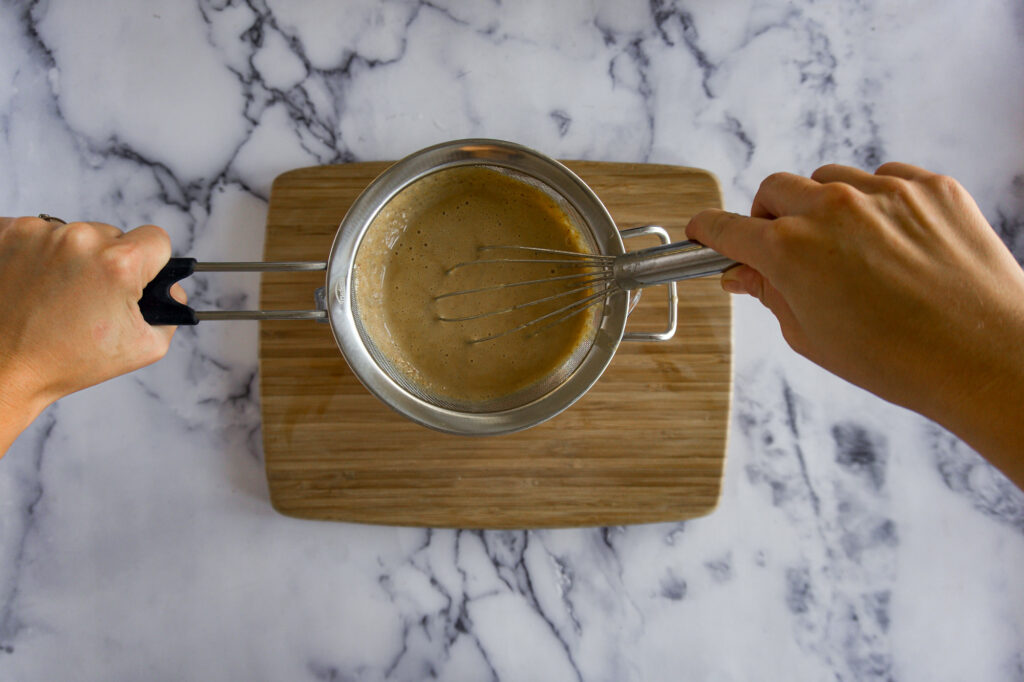 Running a whisk around the strainer to help it strain faster.