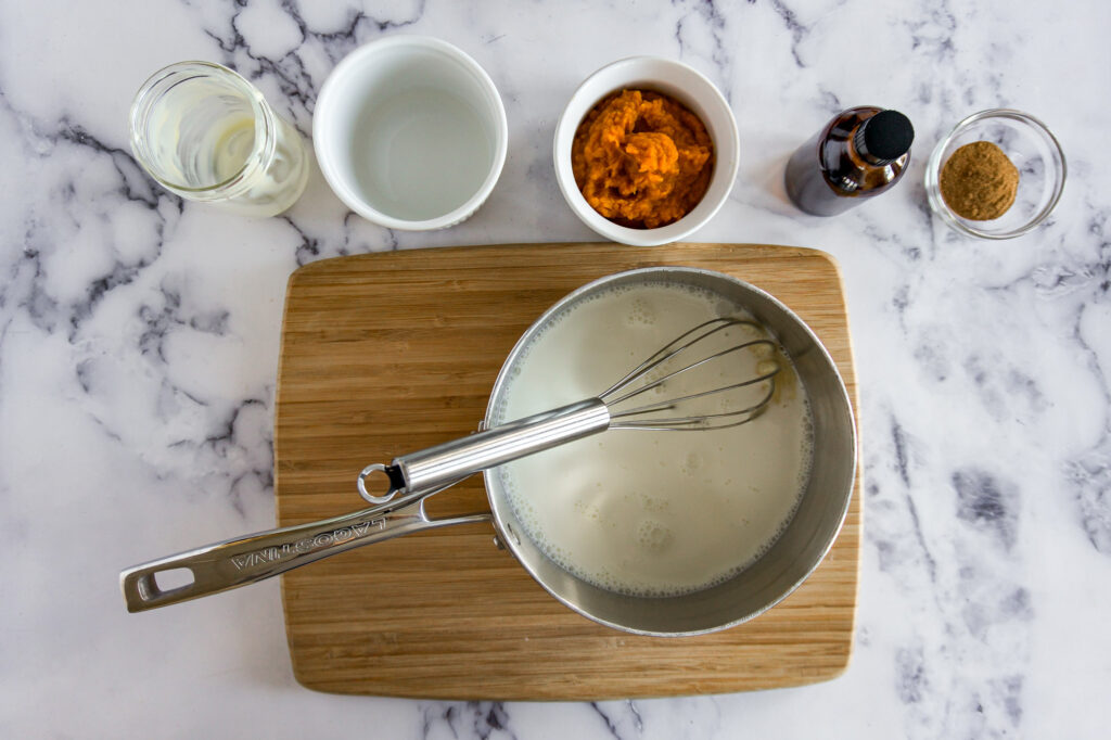 Whisking the cream and sweetened condensed milk together.