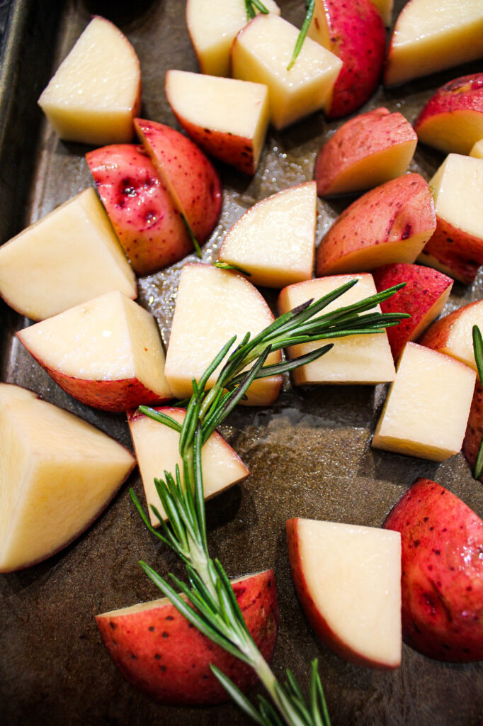 Chopped red skin potatoes on a baking sheet with rosemary sprigs.